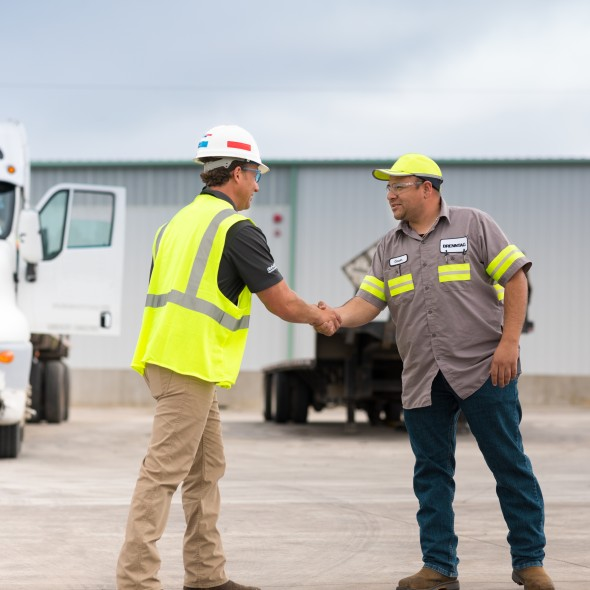 Aaron Booth shaking hands with a worker