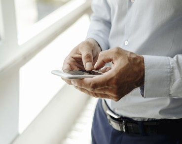 Close-up of businessman at the window using cell phone