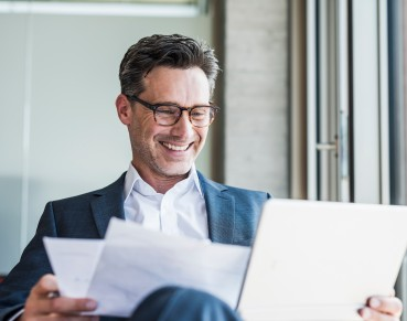 Portrait of laughing businessman with documents