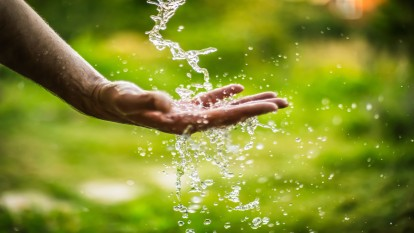 Water falling onto a hand in a field